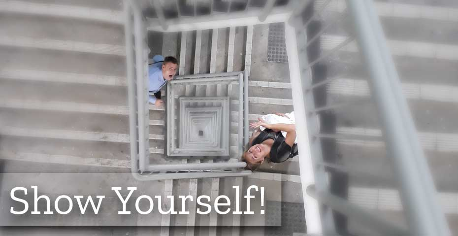 Picture shows two people taking the steps on a staircase and looking up, looking back to the camera to gain attention.
